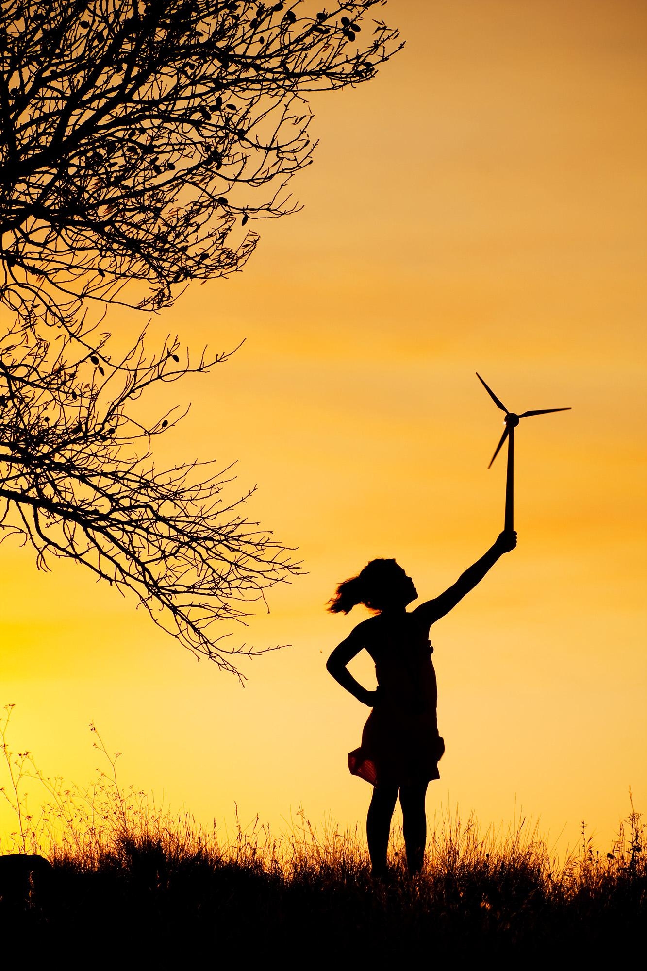 Child holding up a small wind turbine.